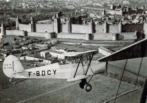 """Un """"Stamp SV-4"""" survolant la Cité de Carcassonne en 1952."""