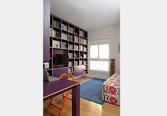 O mesmo ambiente acomoda escritório, home theater e biblioteca no projeto da arquiteta Bruna Riscali. Para isso, ela projetou uma estante na cor berinjela, executada pela Madesma Marcenaria