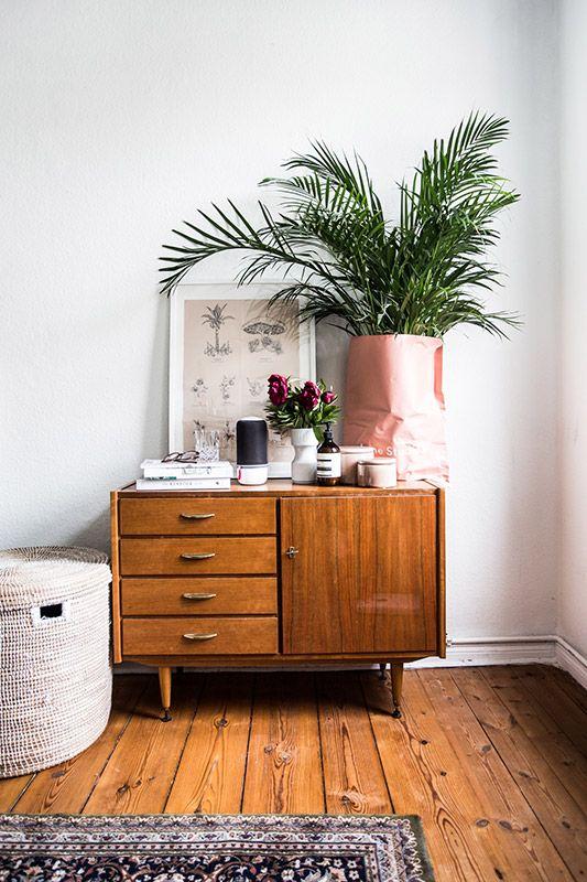 Auf der Vintage Kommode steht eine schoene Dekoidee: Die Acne Studio Tuete mit Pflanze