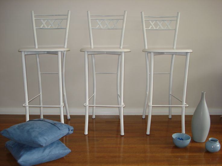 Three white bar stools. The aluminium frames have been sprayed white, with a high gloss finish. The timber seats have been painted in a white chalk paint to give it a streaky effect, and then sealed with varnish for everyday use.