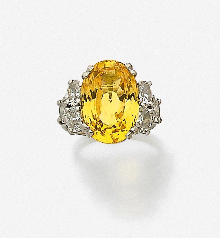 Bague en or gris 18k (750) ornée d'un saphir jaune ovale épaulé de six diamants ovales Poids du saphir jaune: 10.73 cts Tour de doigt: 48, Poids brut: 9.014 g  Accompagné d'un certificat du laboratoire du LFG (2016) indiquant origine du Sri Lanka, sans traitement thermique.  Estimation : 8.000/10.000€