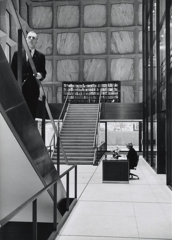 Photograph of unidentified man ascending stairs and unidentified woman seated at front desk at the Beinecke.