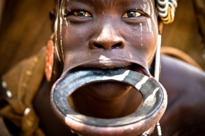 Considered a sign of beauty in the Mursi tribe of Ethiopia Africa, the lip plate is worn by women daily who seek acceptance and to appear desirable to men. When the women are ready to marry, they begin the process of the lip plate by making a hole in the lower lip with a wood stick which is expanded a little everyday. Eventually, when the hole is big enough, women insert a plate and gradually the plate is replaced by a bigger plate until it has reached its full size. It is a very painful process which girls have to undergo for months, where somtimes the teeth have to be broken to insert the plate, but once suceeded, they are seen as the epitome of beauty! also, the bigger the plate, the more beautiful the woman..    The plate is a usually a sacred object and dyed and decorated according to the wearers preference. Women are also shaved, like the men, because they hate hairiness.: Omo Valley, Mursi Tribes, Wood Sticks, Woman, Traditional Lips, Ethiopia Africa, Lower Lips, Culture, Lips Plates