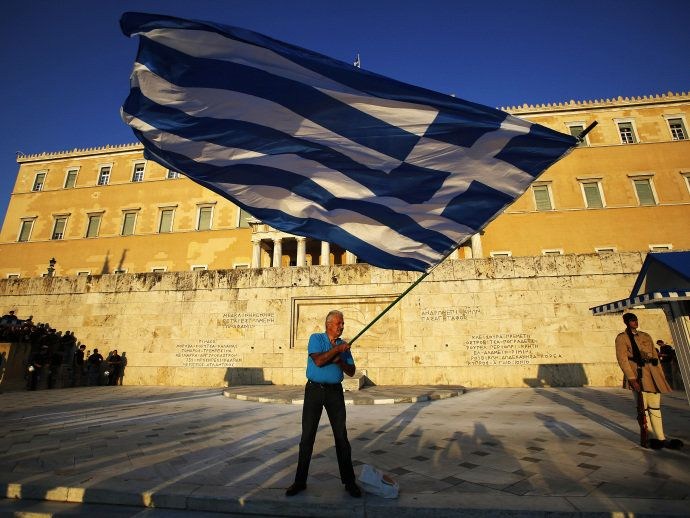 Manifestante pró-euro agita uma bandeira grega em frente ao Parlamento enquanto a polícia de choque, bloqueia a entrada do edifício durante um comício na Praça Syntagma, em Atenas - 09/07/2015