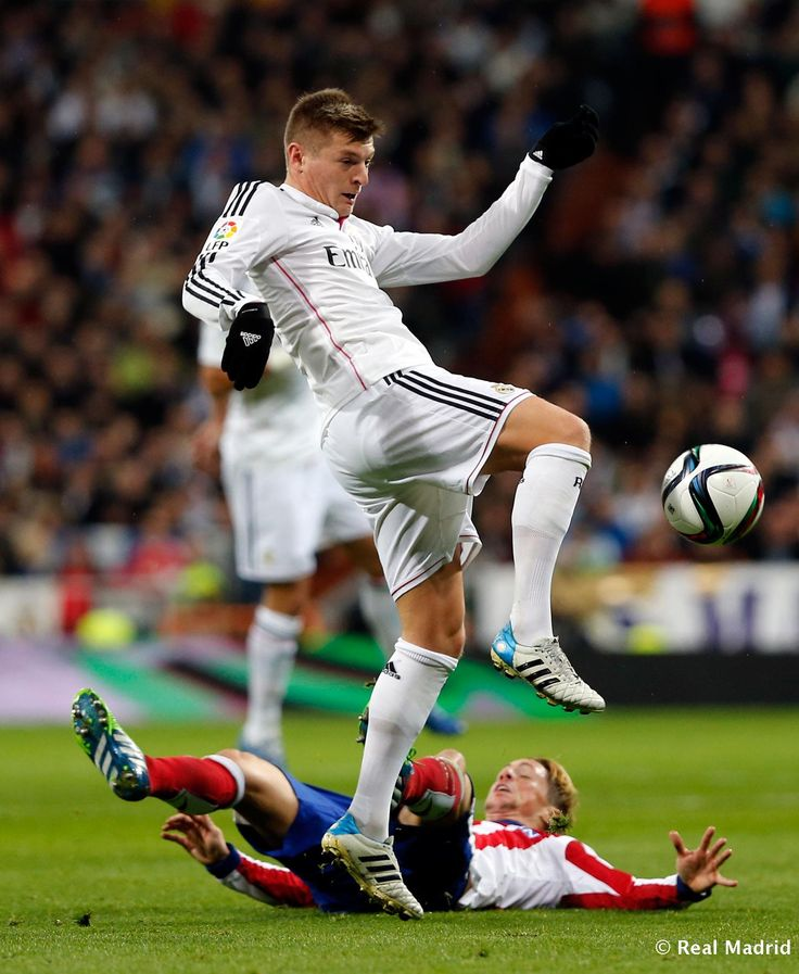 Toni Kroos of Real Madrid in action against Fernando Torres of Atlético de Madrid during the Copa del Rey round of 16 second leg match between Real Madrid and Atletico de Madrid at Estadio Santiago Bernabeu on January 15, 2015 in Madrid, Spain.