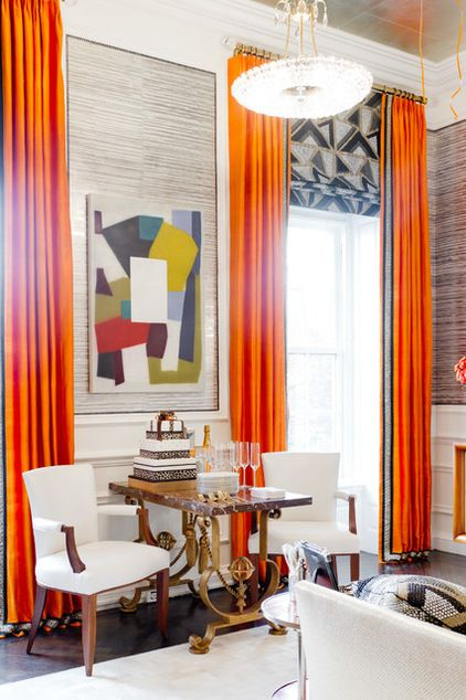 Fantastic room with abstract art, a gorgeous more traditional table, and exquisite window treatments: shades in a cubist print & vibrant orange panels with a coordinating border.
