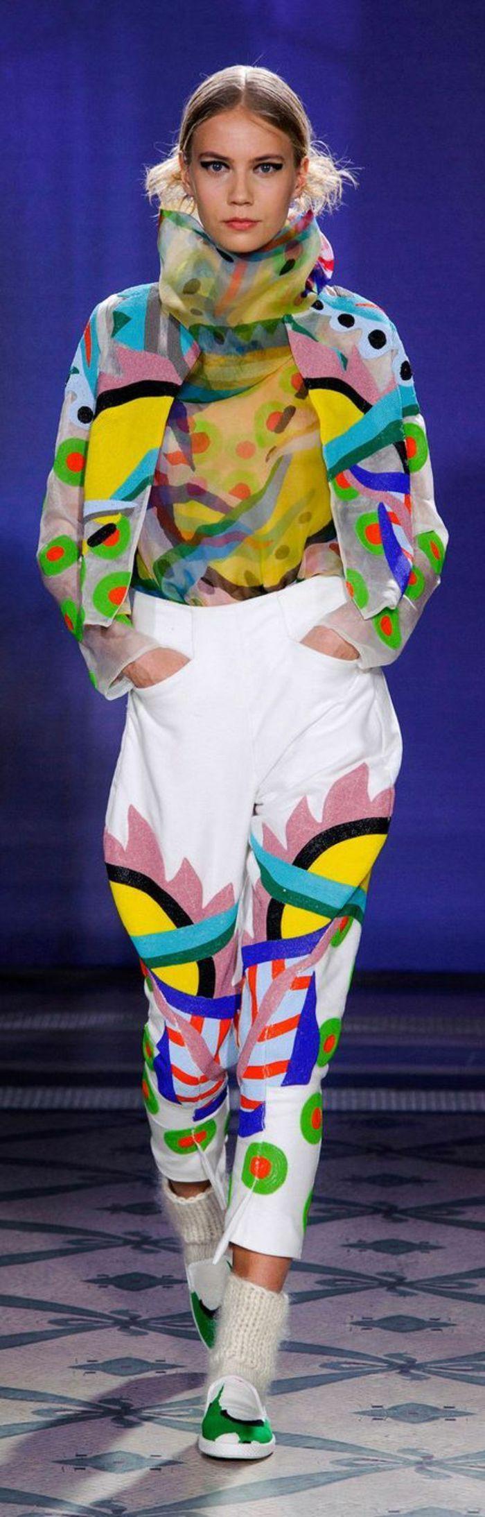 mode année 80 pantalon blanc avec des motifs géométriques aux couleurs ensoleillées et veste et blouse hautes en couleurs vives