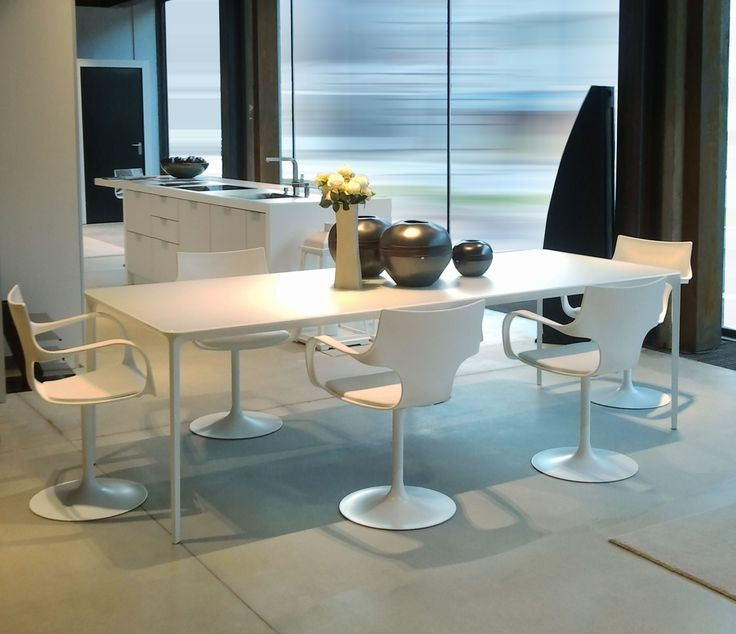 Slim white table and white Flute chairs. Minimalism and design in the kitchen space.