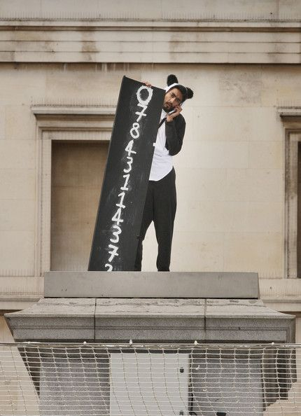 Sri Lankan fine art graduate Suren Seneviratne stands on the empty fourth plinth with his mobile phone number on display in Trafalgar Square on July 6, 2009 in London.