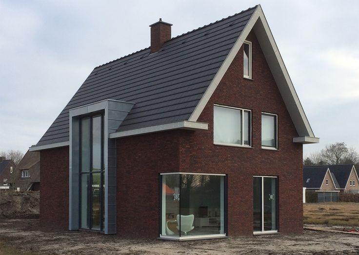 Donkerbruin en paars genuanceerde metselwerk gevelstenen en antraciete vlakke dakpannen. De glazen hoekoplossing op beganegrond en de zinken gevelbekleding met het 5.2m hoge kozijn geven een moderne twist aan de woning..