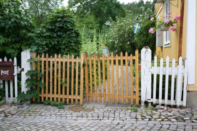 14. Trägrind – Ger en känsla av sommar Dubbelgrindar är praktiska, då man enkelt kan öppna för breda fordon. Här har grinden fått samma utseende som staketet som omger huset. Endast rytmen mellan långa och korta spjälor skiljer lite mellan grind och staket. Dubbelgrinden sitter monterad i rejäla grindstolpar av trä. För att synliggöra själva entrén har grindens ribbor lämnats trärena. Ytbehandlingen kan vara olja eller lack. Det är somrigt och fint och passar bra till huse...