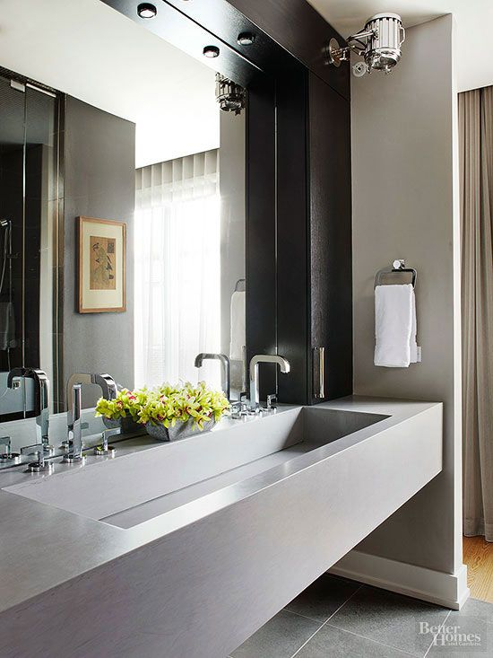 Set high atop a vanity wall, a klieg-style fixture shines a theatrical light on a bathroom's fashion-forward fittings. Small downlights installed in the mirror frame supplement the klieg light to better illuminate daily washroom tasks taking place at the trough sink below.