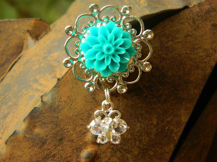 Aqua resin flower on a silver tone metal alloy flower with silver tone metal back pin. Clear rhinestone butterfly connected with a silver split ring. Length 4 cm, width 3 cm, depth 1.5 cm.  This product can be custom made with different colour flowers and butterflies.  https://www.madeit.com.au/Main/Item?itemId=956810