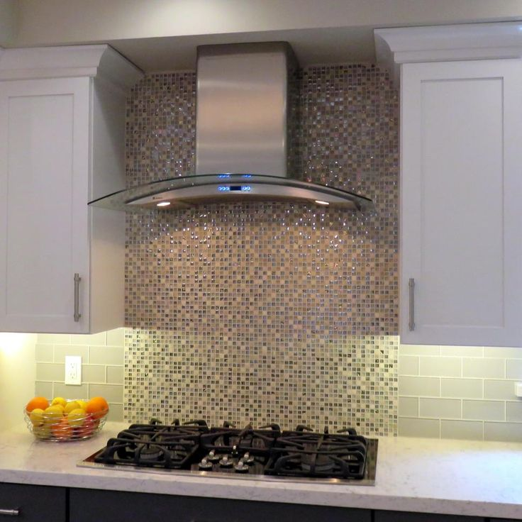 This glass backsplash, tiled in tones of neutral and brown, serves as a beautiful addition and primary design element in a modern kitchen. Using large, coordinating glass tiles everywhere except over the range provides a look of coordination without creating an busy feeling. The range hood has been kept small, allowing the backsplash to be the main focus.
