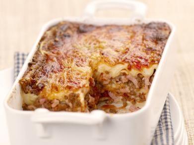 9 lasagnevellen 400 g rundergehakt 150 g bacon (reepjes) 1 ui (grote) 1 teentje knoflook 400 g tomatenblokjes (blik) 200 ml room 120 g emmentaler (geraspt) 1 el tomatenpuree ½ l groentebouillon 4 el olijfolie 1 el boter peper zout  Bereidingswijze 1Verwarm de oven voor op 200°C. 2Laat de kappertjes uitlekken. Borstel de paddenstoelen schoon en snij ze in stukjes. Pel en hak de ui en de knoflook. Hak de noten. 3Kruid de vis met peper en zout. Smelt 30 g boter in een ovenschaal.