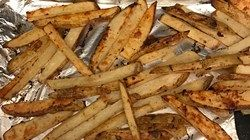 Potato slices are coated in garlic salt and sugar and baked into crispy, golden French fries.
