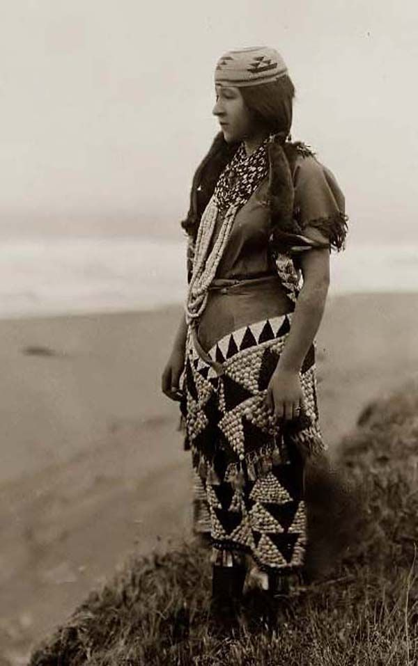 Here is an extraordinary photo of an Indian Woman's Dress. It was taken in 1923 by Edward S. Curtis.    The photo documents Ada Lopez Richards, in a full-length portrait, standing near the shore wearing a hat, necklaces, and dress.    We have compiled this collection of photos mainly to serve as a vital educational resource. Contact curator@old-picture.com.: