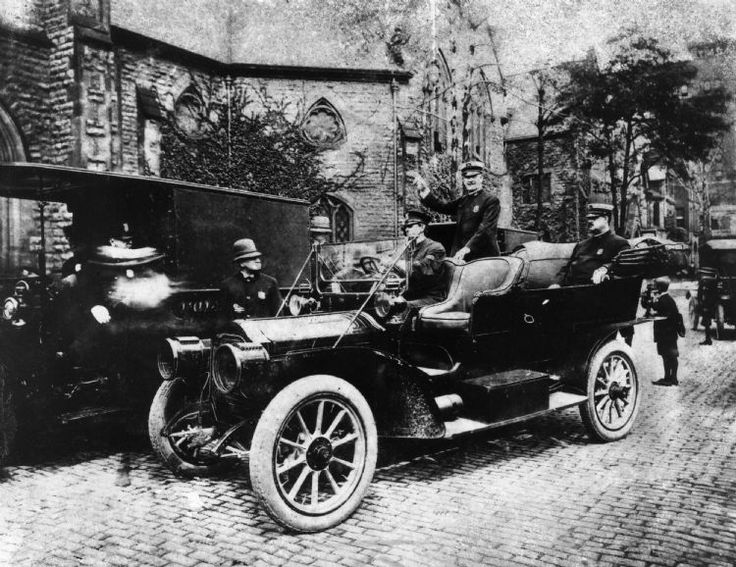 This may be the city's first police car. It appears to be a Packard from around 1909 or 1910, the vintage purchased for the department by Frank Croul. The officer standing in the backseat is identified as Burton Girardin, grandfather of Ray Girardin, who was police commissioner in the 1960s. (The Detroit News) Album ID: 1370996 Photo ID: 39102393