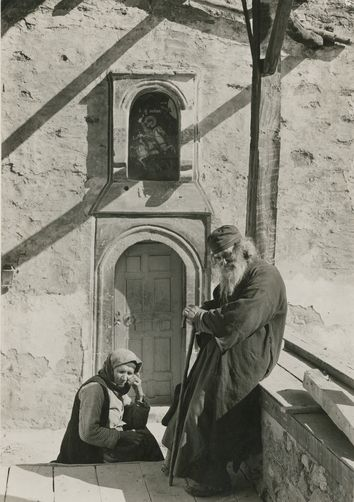 A Greek monk and his wife sit outside of Saint George convent, Feneos, 1900s Location: Peloponnesus, Greece. Photographer: FRED BOISSONNAS/National Geographic Creative