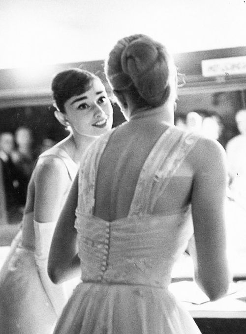 Audrey Hepburn and Grace Kelly share some words backstage at the 28th Annual Academy Awards, 1956.
