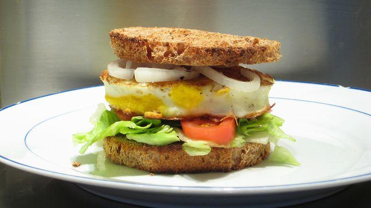 Бургер с баклажанами   Этот бургер – настоящая находка для вегетарианцев. Необычное сочетание баклажанов и изюма сможет разнообразить меню.   Понадобится: баклажаны – 2 штуки, хлебные крошки (панировка) – 300 гр., яйца – 6 штук, пармезан – 100 гр., изюм – 80 гр., обжаренные кедровые орешки – 70 гр., консервированный зеленый горошек – 6 столовых ложек, мука – 70 гр., помидор – 1 штука, йогурт – 200 гр., цельнозерновые булочки – 4 штуки, лук репчатый – по вкусу, перец чили – по вкусу.  Изюм…