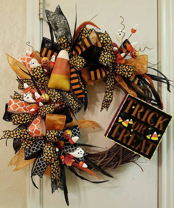 Trick or Treat  This charming Candy Corn wreath was handmade using a natural grapevine wreath base adorned with lots of premium wired ribbon. Trick or treat sign lights up to let your ghosts and goblins know where the candy is at. Adorable 5 primitive candy corn with lots of little ghost and candy corns sprinkled all around. This wreath would look wonderful on your front door, above your mantel, over a mirror, or on an interior wall. This is the perfect wreath for Halloween.  This wreath…