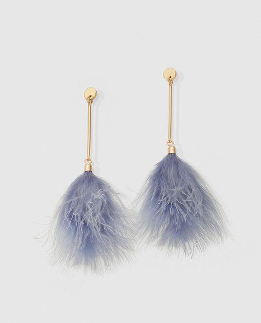 Pendientes largos de metal dorado teminados en un plumero de color azul.