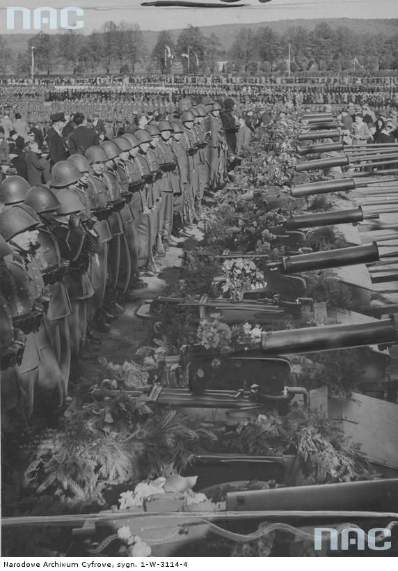 Przekazanie 1 Morskiemu Batalionowi Strzelców sztandaru i 11 ciężkich karabinów maszynowych ufundowanych przez społeczeństwo powiatu wejherowskiego Strzelcy 1 Morskiego Batalionu Strzeleckiego przy, udekorowanych wiązankami kwiatów i gałęzi, ciężkich karabinach maszynowych 7,92 mm Browning wz. 1930 na biedkach piechoty. Uroczystości przygladają się liczni mieszkańcy Wejherowa i okolic. Źródło NAC