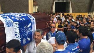Image caption                     Los ecuatorianos comienzan a enterrar a las víctimas del terremoto.   Es un momento profundamente triste, pero la música es animada y la gente da palmas para intentar mantener alta la moral a pesar del luto. En el cortejo fúnebre de Joselo, en El Carmen, está claro que el hombre fue un fanático del fútbol: su ataúd tiene la bufanda de su equipo y quienes lo cargan van vestidos con la camiseta azul de su club. Según