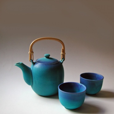 The color on this Japanese tea set absolutely pops, and the subtle color gradient detail is what makes this item truly cool. Matte ceramic. Set includes pot with bamboo handle and two tea cups.
