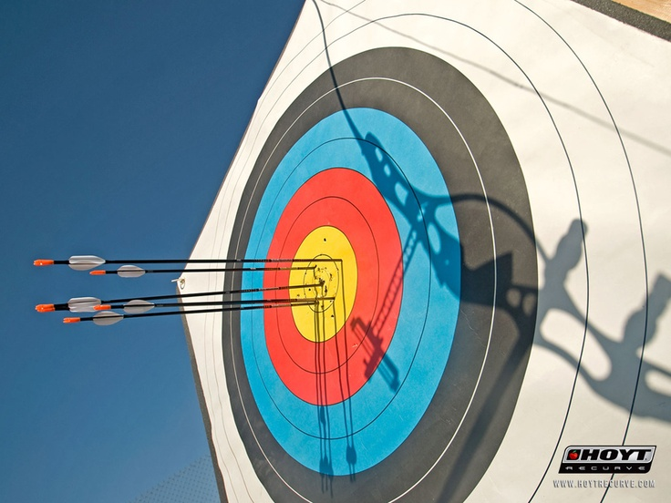 Cool photograph of archery target with shadow of Olympic recurve bow.