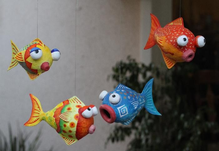 Four fish made of paper mache, painted with acrylic paint. Hanging mobile. Each fish is about 7x5 inches.