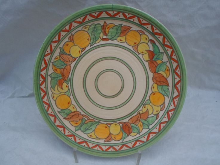 A 1930s Crown Ducal wall plaque, designed by Charlotte Rhead in the 5802 Fruit Border (green variation) pattern, having a tube-lined decoration of circular fruit and leaves on a plain ground, printed and tubed marks verso to include a Rhead facsimile signature, 32cm diameter