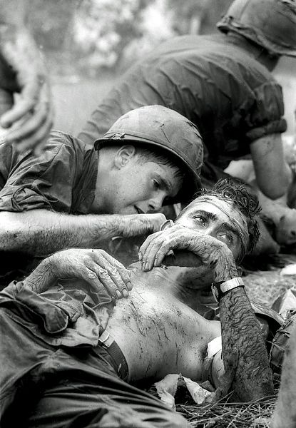 Henri Huet. Medic James E. Callahan of  Pittsfield, Mass., treats a U.S. infantryman who suffered a head wound when a Viet Cong bullet pierced his helmet during a three-hour battle in war zone D, about 50 miles northeast of Saigon. June 17, 1967