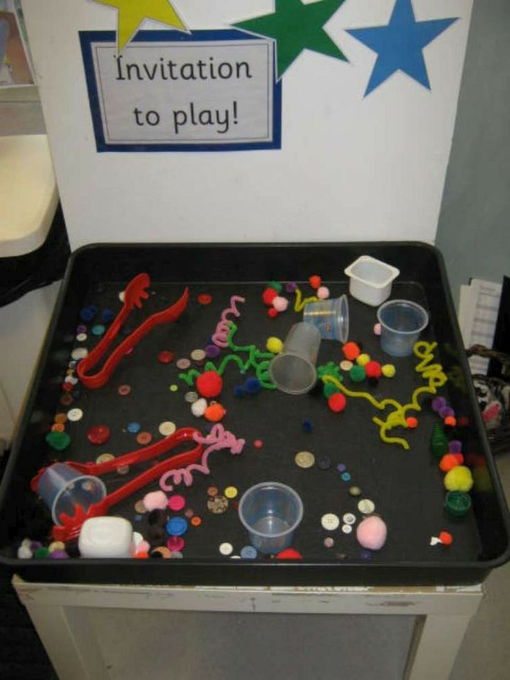 Kidsunlimited Stourton set up trays with large plastic tongs to encourage children to pick up the pompoms, buttons and pipe cleaners and put them into the cups