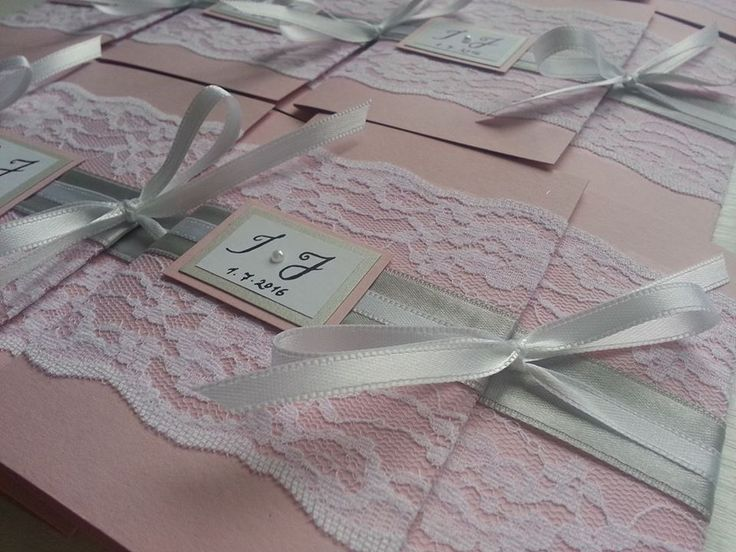 Romantic wedding invitation covered with lace and silver ribbon.