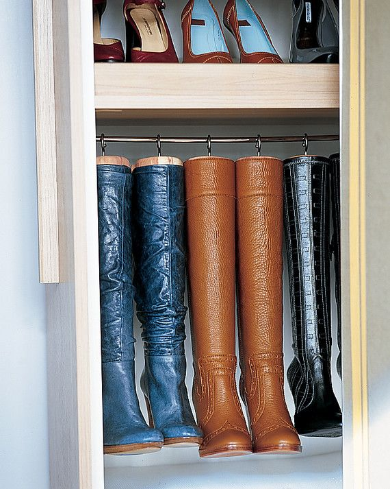 Homemade hangers preserve the shape of tall boots and maximize space. They're created by replacing the knobs on cedar boot trees with large cup hooks, which are screwed into the tops. The trees and boots then hang from a cafe-curtain rod.