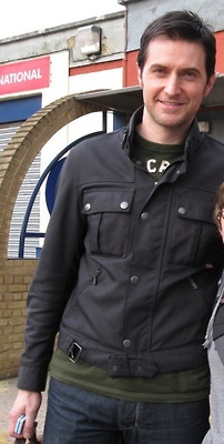 Richard Armitage    Oooh, new. Where's that from?  I think it's a behind the scenes of Spooks pic….early season 8 :)  Yeah - looks like the Belstaff look from season 8, doesn't it? And the lucky fan has been cut out ;-)
