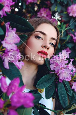 Beautiful girl in the bushes with large leaves