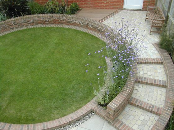 Simple, stylish garden design with a round lawn for a slight slope and a scrim of Verbena bonariensis (Outdoor Creations - Professional Small Garden Design Portfolio).