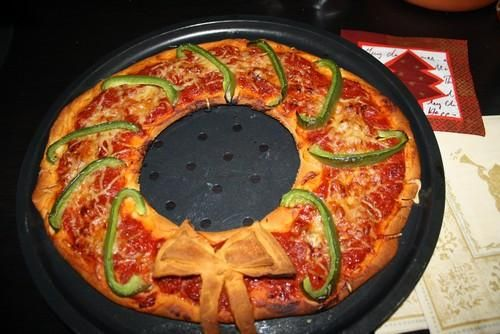 Pizza Kerstkrans. Deeg uitrollen met een kookring een gat uitsnijden en bewaren voor de strik. Beleggen en afbakken.