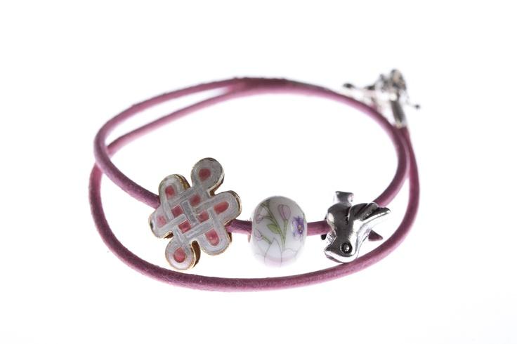 """Chic Victim » Brățară piele roz: """"Minnie""""  Brățară din piele naturală roz cu elemente din metal comun de culoare argintie, element cloisonne și bilă din porțelan. Face parte din colecția """"Minnie"""". Componentele din metal sunt din aliaje antialergice, nu conțin nichel și nici plumb, dar își pot schimba culoarea în timp sau în contact cu unele tipuri de piele."""