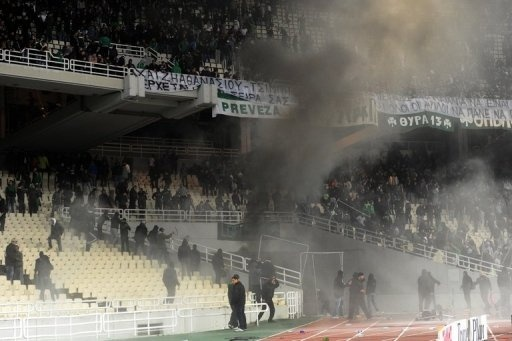 Riot police clash with Panathinaikos supporters during the Athens derby against Olympiakos on March 18, 2012. Olympiakos were officially awarded their 39th Greek league title on Wednesday after the Hellenic Football Federation upheld a decision to punish second-placed Panathinaikos for crowd trouble at last month's Athens derby. (AFP)