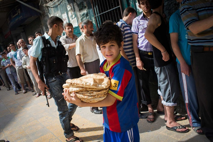 The 24 Most Inspiring Photos of 2012 // A boy waits holding a stack of flatbreads in Syria during The Battle of Aleppo on August 30, 2012.