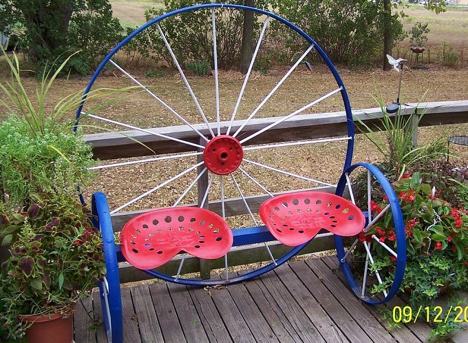 welded bench using one large and 2 matching antique wagon wheels & 2 tractor seats