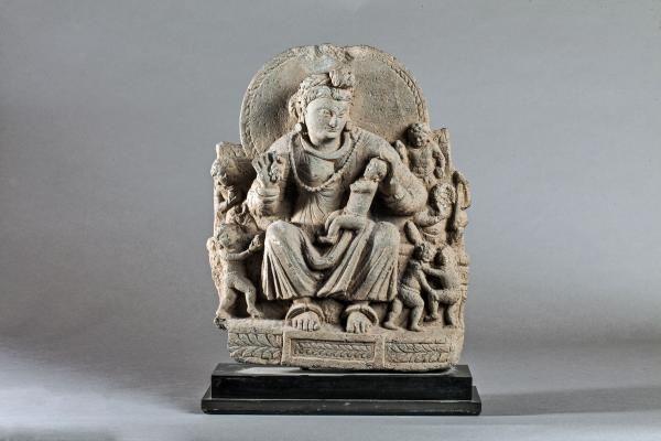 Stèle illustrant Hariti assise vêtue d'une robe plissée parée de joyaux et coiffée d'un serre tête tressé à médaillon floral. La déesse Bouddhique de l'harmonie de la famille est entourée de sept enfants. Pierre schiste gris. Pakistan. Afghanistan. Art Gréco Bouddhique du Gandhara. 3 ème à 5 ème siècle.  45cm.