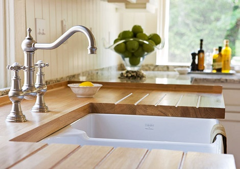 Farm-style sink topped with an oak work surface, which is routed with grooves to drain water.