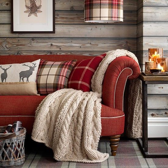 myidealhome: classic & cosy country charm (via housetohome.co.uk) - gorgeous red sofa with cable knit throw. The woodsy planked wall looks equally cozy.