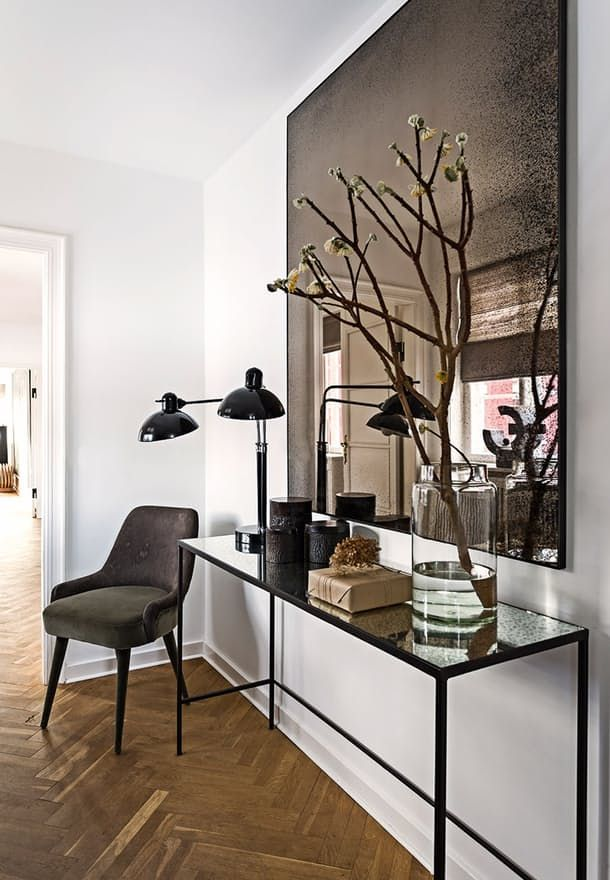 Modern entryway with a long console table, upholstered velvet chair and a large mirror.