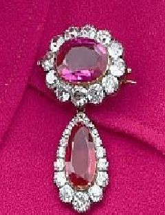 Queen Victoria's Crown Ruby Brooch. purchased along w/ necklace and earrings, from Garrard in 1854 by QV. Originally consisted of Opals and Diamonds. It's said that around 1902 Queen Alexandra, Queen Consort altered pieces by replacing Opals w/rubies, per Suzy Menkes, of The Royal Jewels, brooch not altered until 1926. Worn by Queen Elizabeth, Queen Mother with rest of parure and Oriental Circlet Tiara. Not seen since death in 2002 but worn by QEII on 6/16/2015 to Royal Ascot, Day 1.